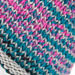 Bildet viser et nærbilde av en lue strikket i sari re-silkegarn.