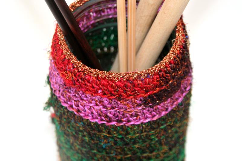 Sari re-silkegarn er silkegarn spunnet av rester av silkestoffer. Når skredderne klipper ut og skal sy saronger så benytter skredderne seg av restene og spinner dette til garn. Garnet kan anvendes på mange forskjellige måter. Her har man heklet rundt et norgesglass hvor det er plass til lange strikkepinner, som avslutningskant er det heklet i et bronsjefarget glittergarn. Bildet viser nærbilde av dette.