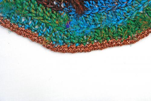 Sari re-silkegarn er silkegarn spunnet av rester av silkestoffer. Når skredderne klipper ut og skal sy saronger så benytter skredderne seg av restene og spinner dette til garn. Garnet kan anvendes på mange forskjellige måter. Her har det blitt heklet en brikke hvor avslutningskanten er heklet i en bronsjefarget glittertråd.