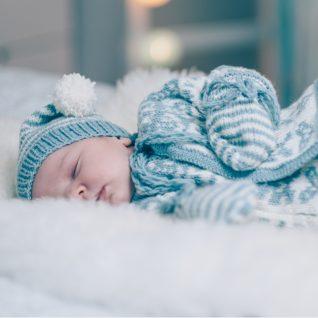 Hentetsettet velkommen til verden er en strikkepakke til baby. Her ser vi bildet av babyen som ligger på siden med ansiktet vendt mot kamera. Bildet er fra midjen og opp.