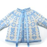 Hentesettet velkommen til verden er en strikkepakke til baby. Her ser vi hele jakken som ligger flatt med åpningen i front.