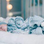 Hentesettet velkommen til verden er en strikkepakke til baby. Her ser vi babyen ligge på siden i helfigur. Han har settet på seg. Ansiktet er vendt mot kamera.