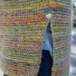 strikkepakken camelona i fabel og kidsilk erle. Her ser man splitten på genseren hvor det er isydd en knpp over.