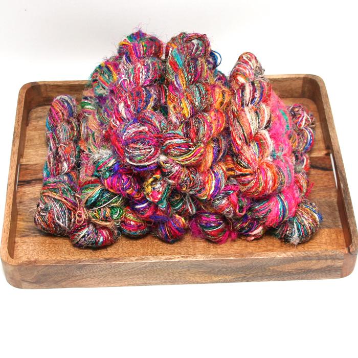 Recycled sari silk yarn. Flere hesper ligger på et bord.