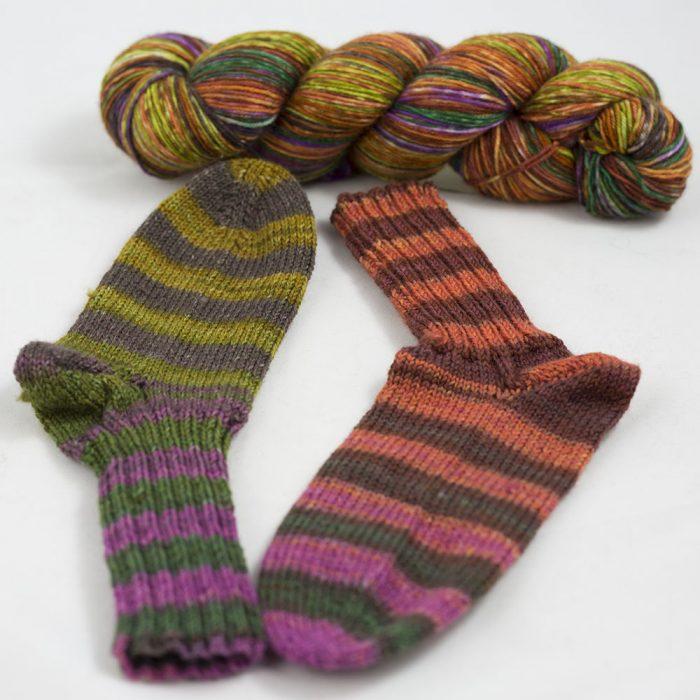 Bildet viser en hespe og et par sokker i det ferfarget Lazy Rock Yarn fra Krenke soul wool. Her i fargen Indian summer.