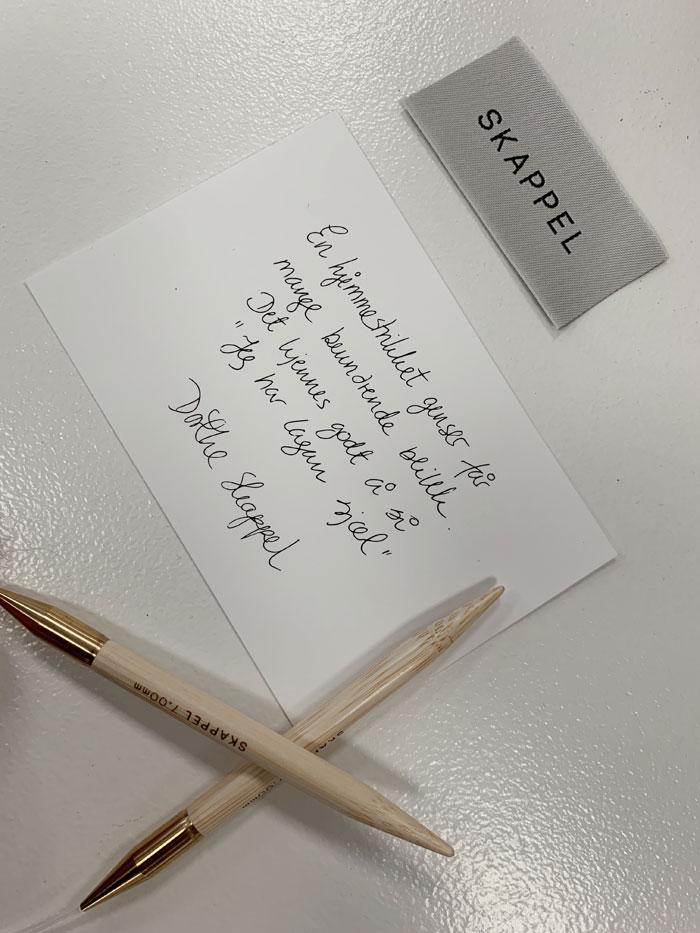 Bilde viser et kort som ligger på et bord sammen med en strikkepinne og en brandtag i et stoffmateriale hvor det står skappel. På kortet står det en hilsen fra Dorthe Skappel.