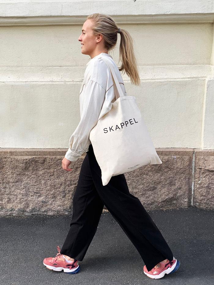 På bildet ser man en ung pike fra siden. Hun går bortover en gate- På venstre skulder bærer hun et strikkenett som er laget i et tøymateriale. Påsen er hvit ofg det står Skappel med sort skrift på posen.
