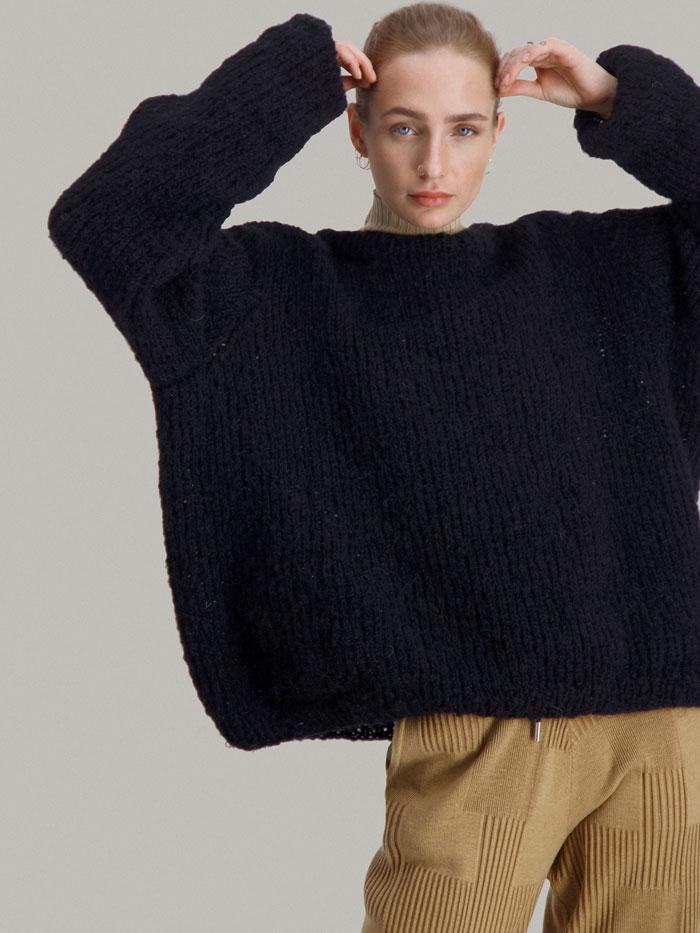 Strikkepakken Leah genser fra Skappel Classic. Bilder viser modellen fra lårene og opp. Begge hendene er passert ved tinningene. Fargen på genseren er svart.