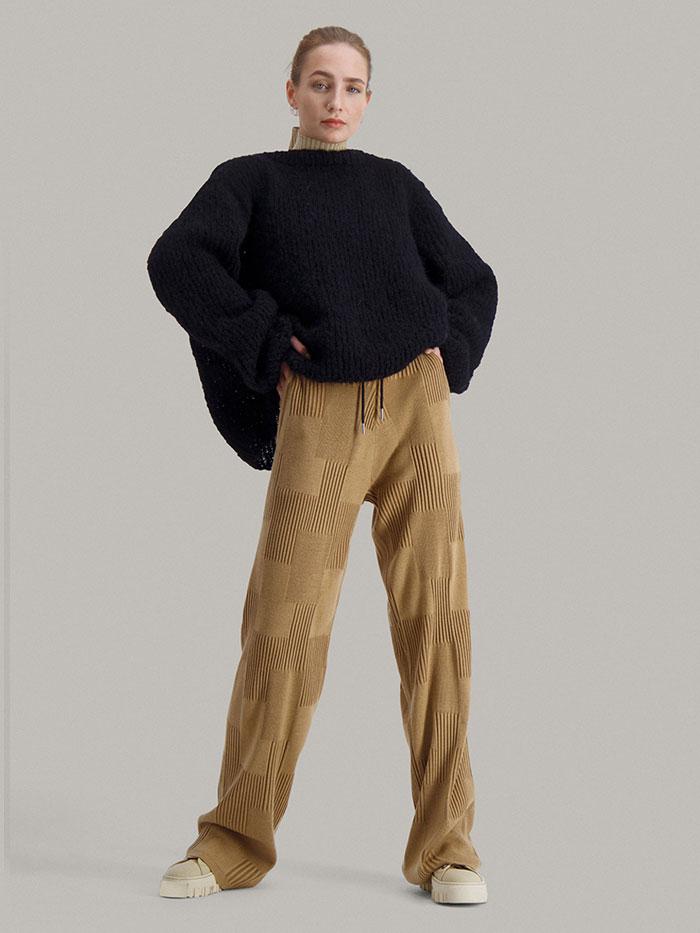 Strikkepakken Leah genser fra Skappel Classic. Bildet viser modellen i helfigur i front. Begge hendene er passert i midjen. Fargen på genseren er svart.