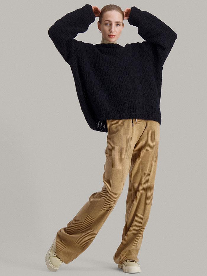 Strikkepakken Leah genser fra Skappel Classic. Bildet viser modellen i helfigur i front. Begge hendene er passert over hodet. Fargen på genseren er svart.
