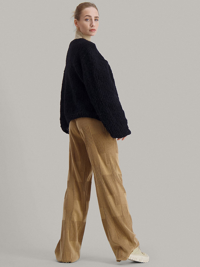 Strikkepakken Leah genser fra Skappel Classic. Bildet viser modellen i helfigur. Kroppen viser delvis bak men ansiktet er vendt i forgrunnen. Begge hendene er passert langs siden. Fargen på genseren er svart.