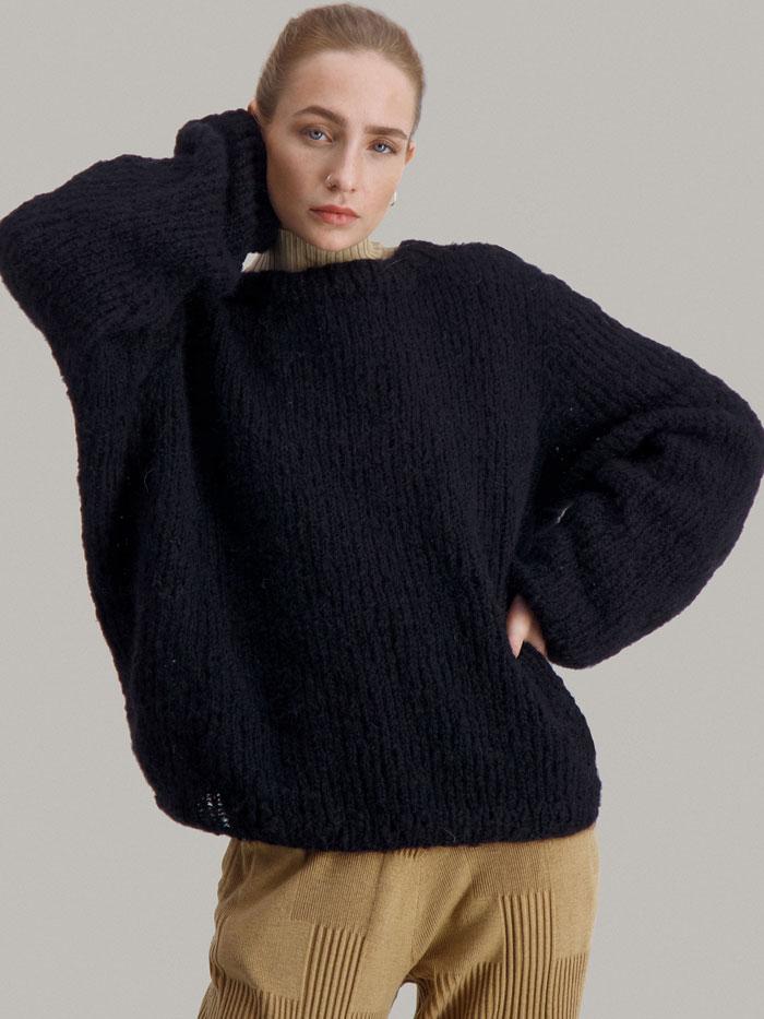 Strikkepakken Leah genser fra Skappel Classic. Bildet viser modellen i halvfigur og i front. Høyre hånd hviler i nakken. Venstre hånd er plasser i midjen. Fargen på genseren er svart.