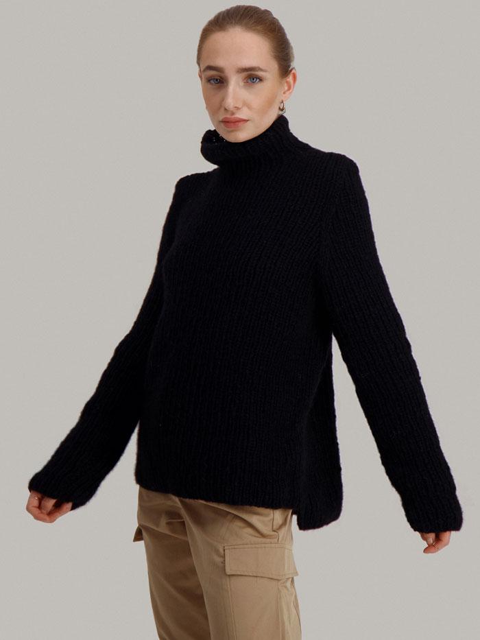 Strikkepakken Lofast genser fra Skappel Classic. Bilder viser modellen i halvfigur fotografert svakt fra siden. Hendene henger nesten ned langs siden. Fargen på genseren er svart.