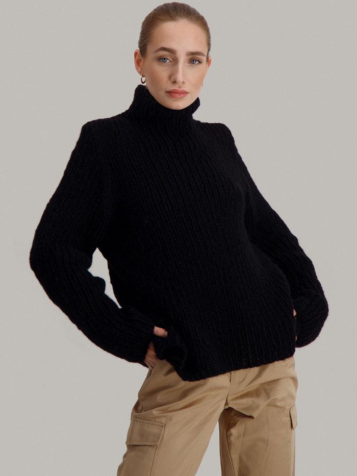 Strikkepakken Lofast genser fra Skappel Classic. Bilder viser modellen i halvfigur fotografert svakt fra siden. Hendene er plassert på hoftene. Fargen på genseren er svart.