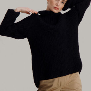 Strikkepakken Lofast genser fra Skappel Classic. Bilder viser modellen fra lårene og opp. Høyre hånd hviler på skulderen. Venstrehånd hviler på nakken. Fargen på genseren er svart.