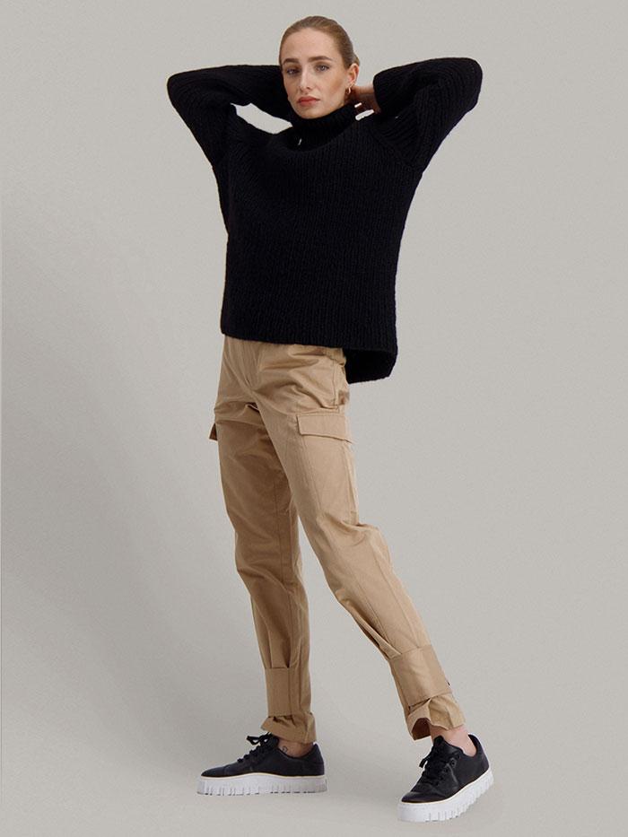 Strikkepakken Lofast genser fra Skappel Classic. Bilder viser modellen i helfigur fotografert svakt fra siden. Hendene er plassert bak på nakken. Fargen på genseren er svart.