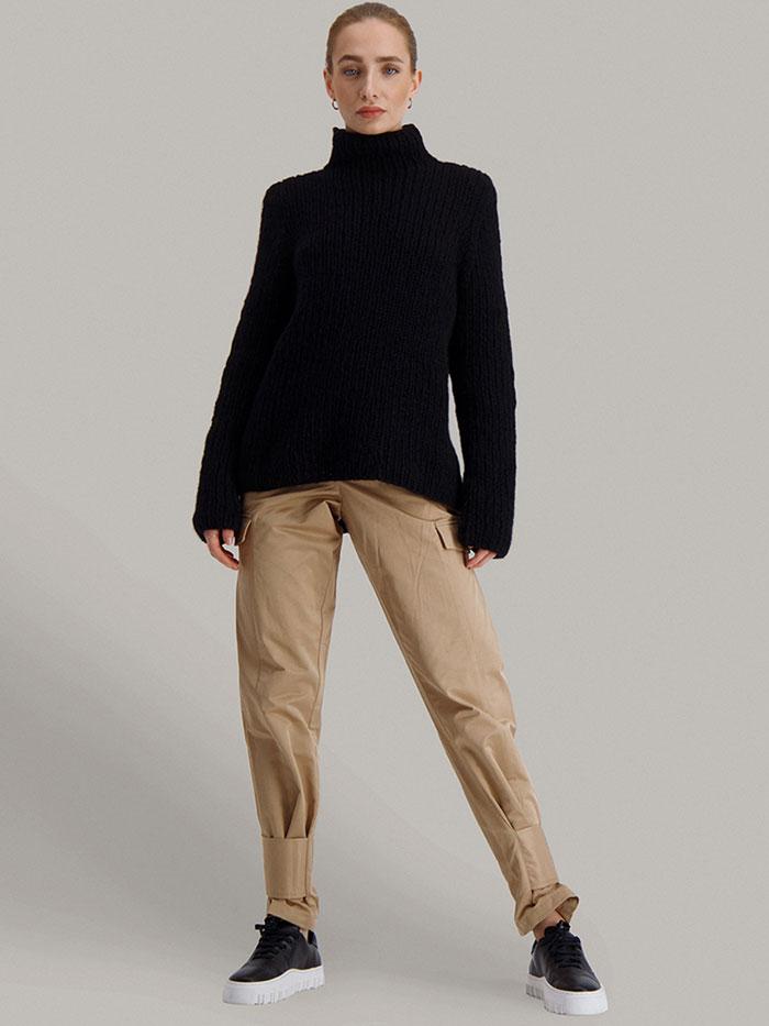 Strikkepakken Lofast genser fra Skappel Classic. Bilder viser modellen i helfigur fotografert i front. Bildet er tatt nedenfra og opp. Hendene henger ned langs sidene. Fargen på genseren er svart.