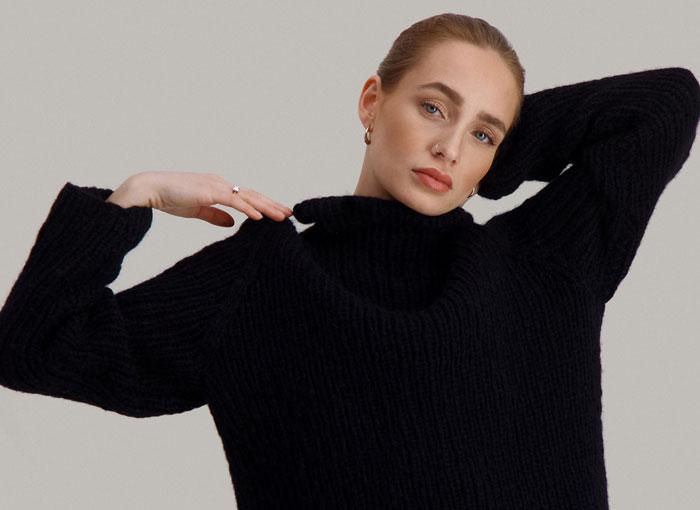 Strikkepakken Lofast genser fra Skappel Classic. Bilder viser modellen fra midjen og opp. Høyre hånd hviler på skulderen. Venstrehånd hviler på nakken. Fargen på genseren er svart.