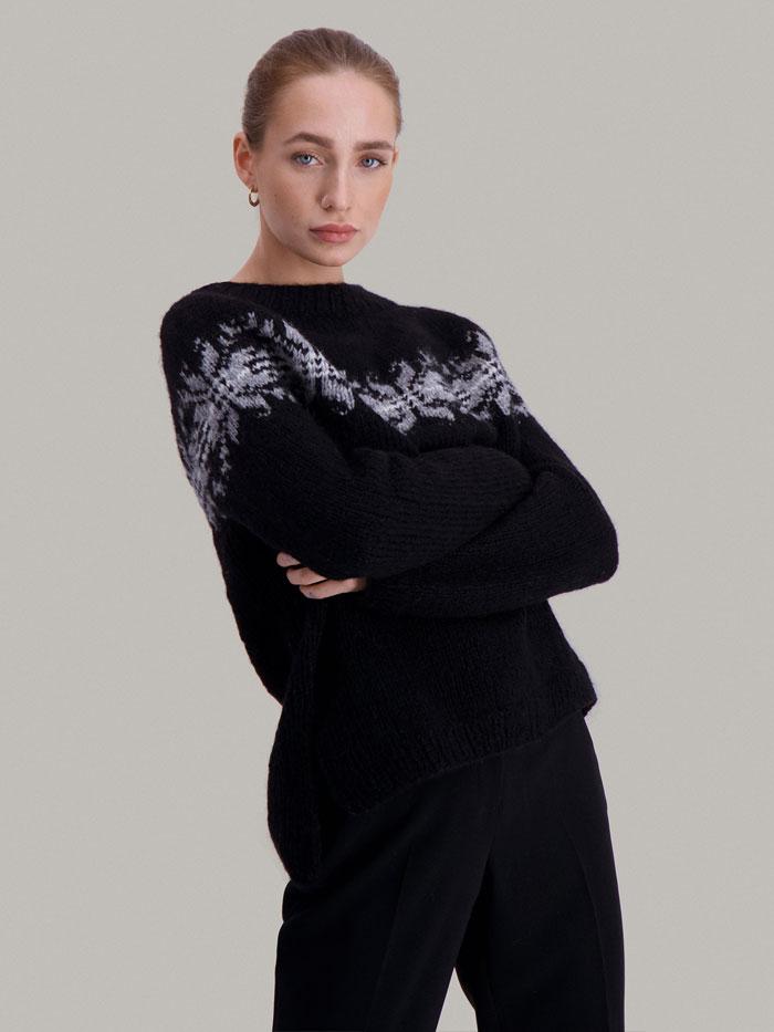 Strikkepakken Osaka genser fra Skappel Classic. Bildet viser modellen i halvfigur og delvis vridd mot front. Hendene hviler i kryss på brystet. Fargen på genseren er blå, natur og grå.