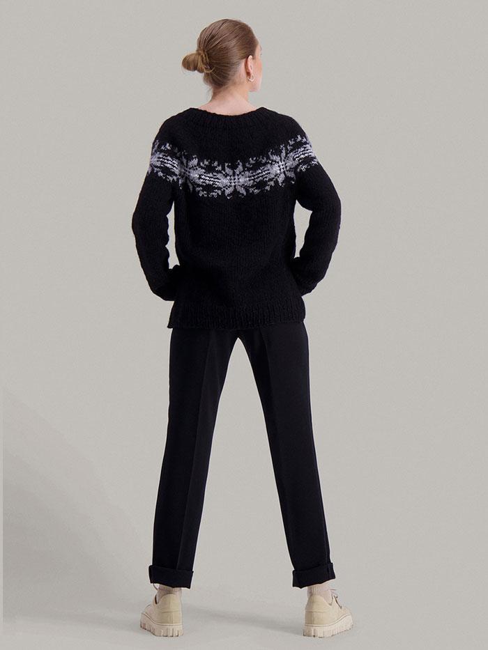 Strikkepakken Osaka genser fra Skappel Classic. Bildet viser modellen i helfigur og fra baksiden. Hendene hviler på hoftene. Fargen på genseren er blå, natur og grå.