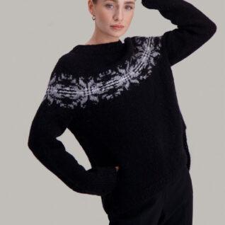 Strikkepakken Osaka genser fra Skappel Classic. Bildet viser modellen fra lårene og opp. Høyre hånd hviler på hoften. Venstre hånd ligger bak hodet. Fargen på genseren er blå, natur og grå.