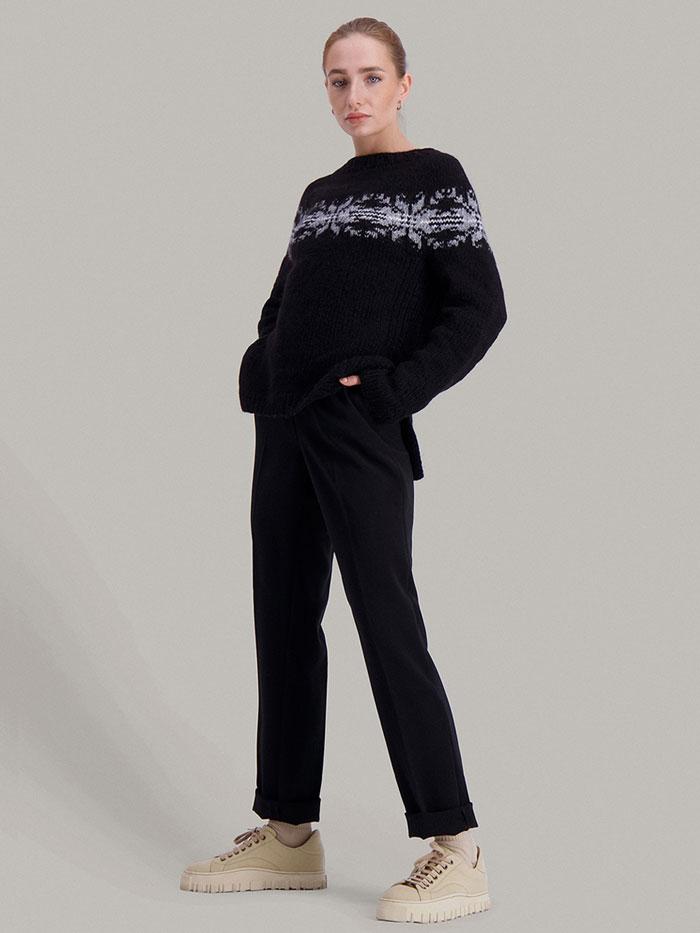 Strikkepakken Osaka genser fra Skappel Classic. Bildet viser modellen i helfigur og kroppen er delvis vridd mot høyre. Hendene hviler på hoftene. Fargen på genseren er blå, natur og grå.