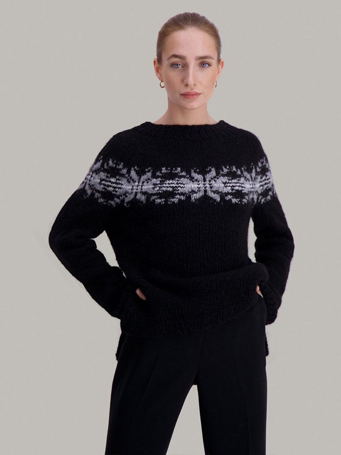 Strikkepakken Osaka genser fra Skappel Classic. Bildet viser modellen fra lårene og opp. Modellen ser rett i kamera. Hendene hviler på hoftene. Fargen på genseren er blå, natur og grå.