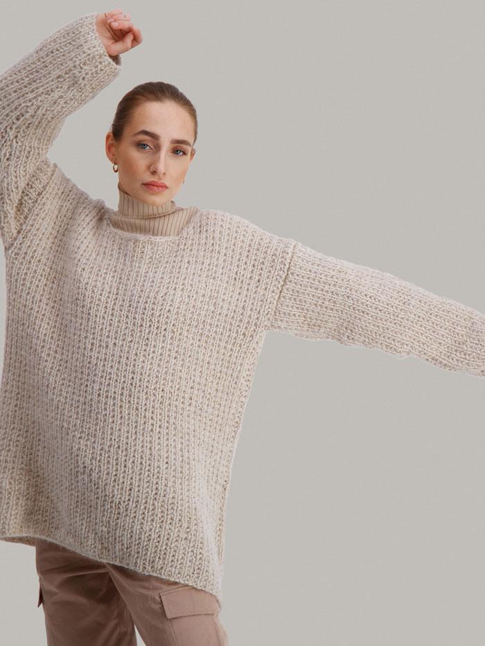 Strikkepakken Dorthegenser fra Skappel Classic. Bilder viser modellen i halvfigur fotografert rett forfra. Modellen holder høyre hånd oppover mot hodet. Venstre hånd strekkes rett ut. Fargen på genseren er sandmelert.