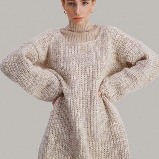 Strikkepakken Dorthegenser fra Skappel Classic. Bilder viser modellen i halvfigur fotografert rett forfra. Modellen holder hendene i siden. Fargen på genseren er sandmelert.
