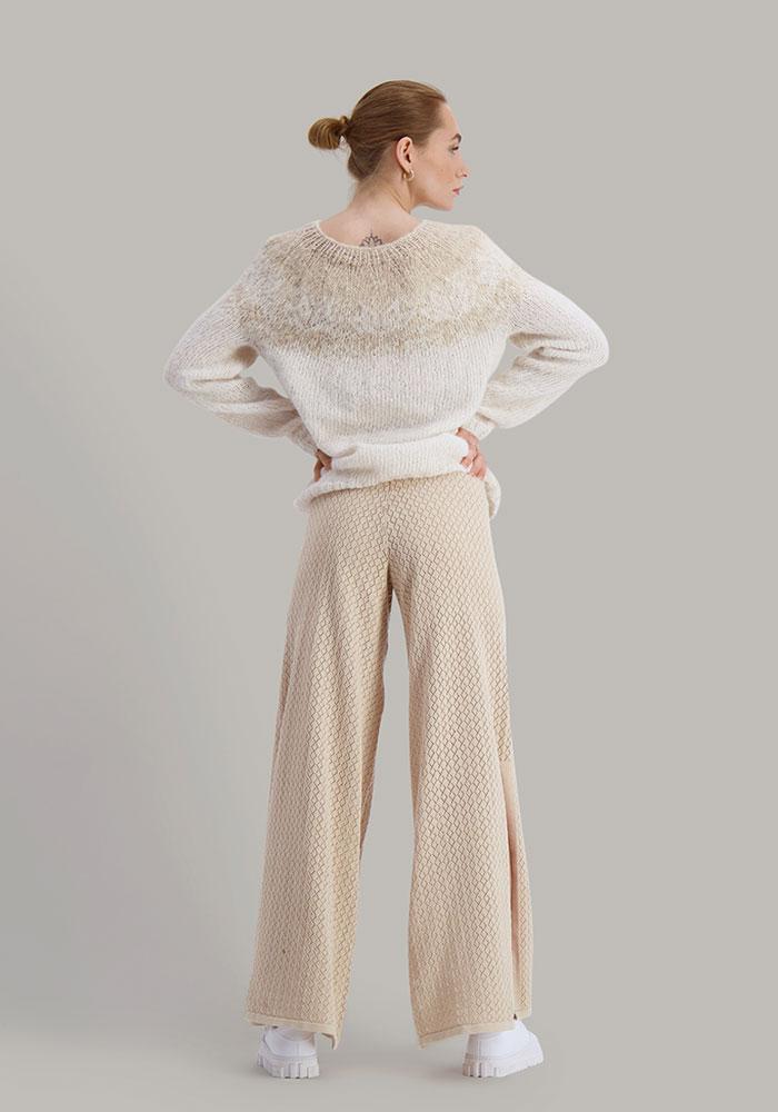 Strikkepakken Flora genser fra Skappel Classic. Bildet viser modellen i helfigur. Modellen står med ryggen til og viser genseren bak. Begge hendene hviler på hoftene. Fargen på genseren er naturhvit og sandmelert.