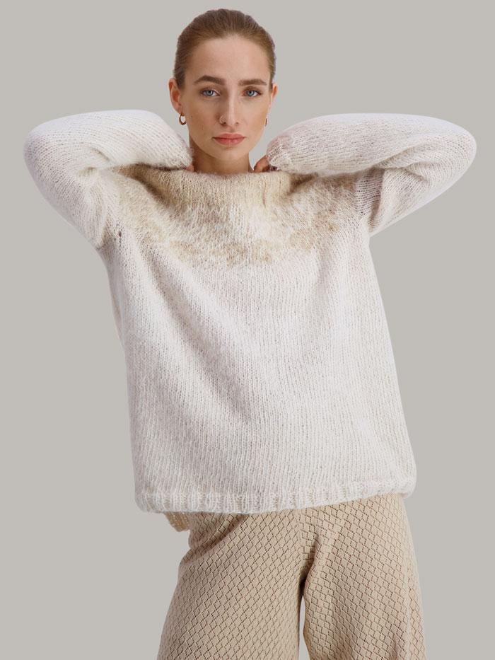 Strikkepakken Flora genser fra Skappel Classic. Bildet viser modellen i halvfigur. Modellen står i front og ser inn i kamera. Begge hendene hviler bak nakken. Fargen på genseren er naturhvit og sandmelert.