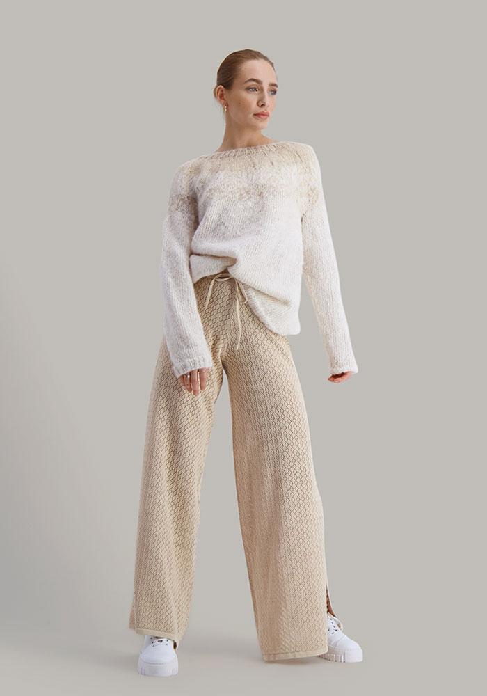 Strikkepakken Flora genser fra Skappel Classic. Bildet viser modellen i helfigur. Modellen står litt skrått i front og ser til høyre. Begge hendene henger ned langs sidene. Fargen på genseren er naturhvit og sandmelert.