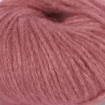 Bildet viser et utsnitt av strikkegarnet Pus fra du store alpakka her i fargen 4048 vinrød.