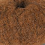 Bildet viser et utsnitt av strikkegarnet Pus fra du store alpakka her i fargen 4050 nougat.