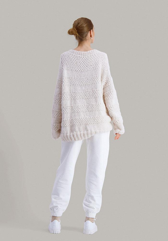 Strikkepakken Solkyss genser fra Skappel classic. Bilder viser modellen i bakfra fotografert. Armene henger ned. Fargen på genseren er hvit.