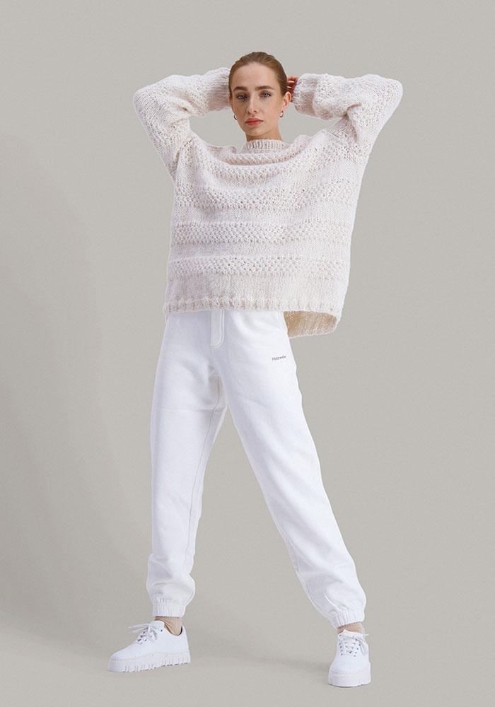 Strikkepakken Solkyss genser fra Skappel classic. Bilder viser modellen i helfigur fotografert forfra. Hun står litt bredbent. Modellen holder hendene over hodet. Her i fargen hvit.