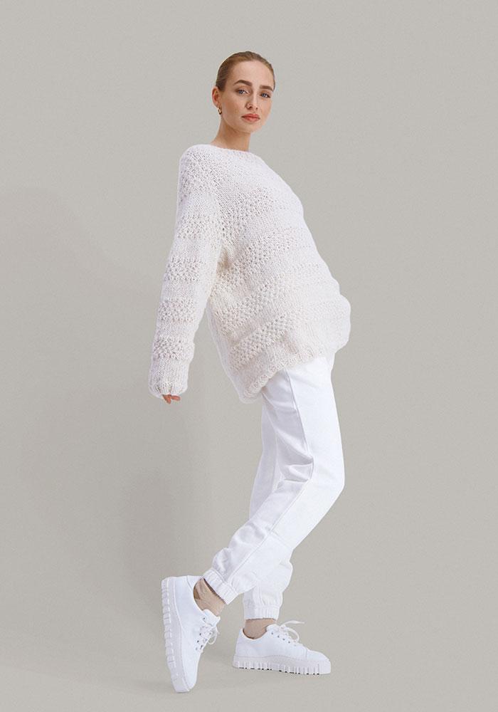 Strikkepakken Solkyss genser fra Skappel classic. Bilder viser modellen i helfigur fotografert fra siden. Modellen holder hendene delvis bakover. Her i fargen hvit.