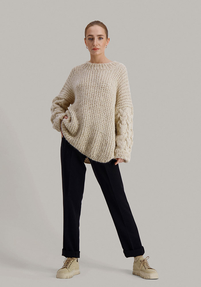 Strikkepakken Sval genser fra Skappel Classic. Bildet viser modellen i helfigur rett forfra. Modellen ser rett i kamera. Høyre hånd hviler i siden og venstre hånd henger rett ned. Fargen på genseren er sandmelert.