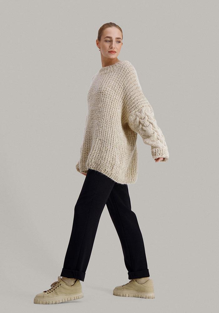 Strikkepakken Sval genser fra Skappel Classic. Bildet viser modellen i helfigur fra siden. Hodet vendes mot front. Høyre hånd henger rett ned. Venstre hånd henger ned men står litt litt ut til siden. Fargen på genseren er sandmelert.