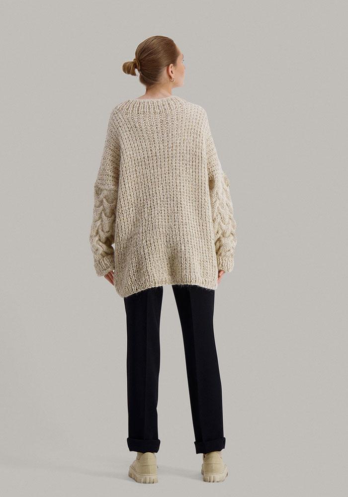 Strikkepakken Sval genser fra Skappel Classic. Bildet viser modellen i helfigur rett bakfra. Begge hendene henger rett ned. Fargen på genseren er sandmelert.
