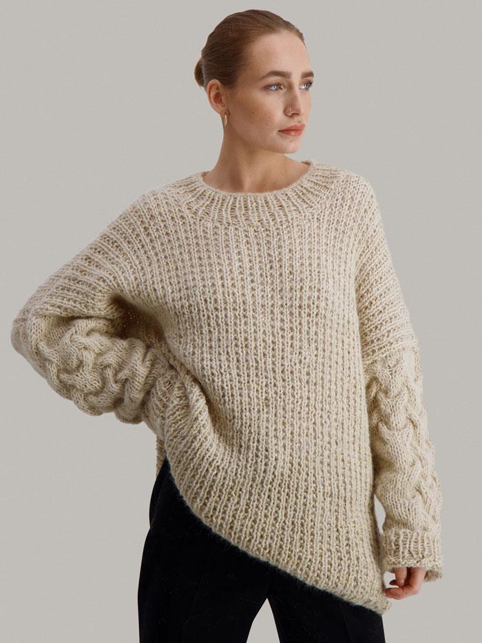 Strikkepakken Sval genser fra Skappel Classic. Bildet viser modellen i halvfigur. Modellen står i front men hodet vendes delvis til siden. Høyre hånd hviler i siden. Venstre hånd henger rett ned. Fargen på genseren er sandmelert.