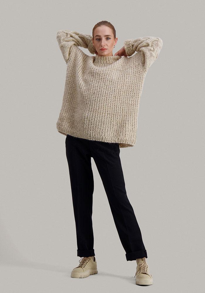 Strikkepakken Sval genser fra Skappel Classic. Bildet viser modellen i helfigur. Modellen står i front og ser rett inn i kamera. Begge hendene holdes bak på nakken. Fargen på genseren er sandmelert.