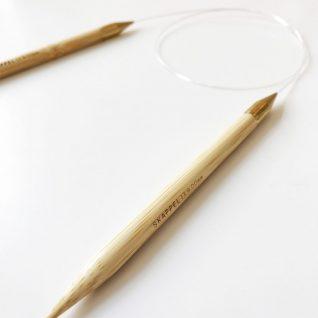 Bildet viser en strikkepinne i tre som ligger flatt på et bord. Leveramdøre er Skappelstrikk.