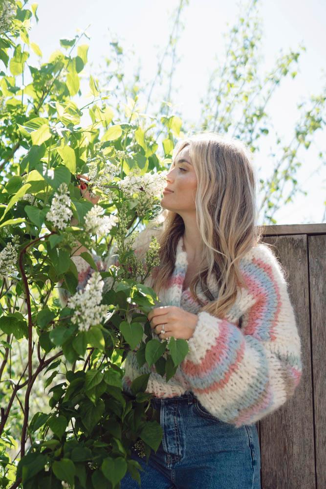 Strikkepakken inneholder mønster og garn fra Camilla Pihl til Wildflower jakke strikket i Fnugg garn. Modellen i halvfigur.