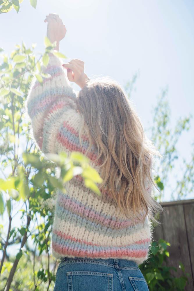 Strikkepakken inneholder mønster og garn fra Camilla Pihl til Wildflower jakke strikket i Fnugg garn. Modellen i halvfigur. Vi ser modellen bakfra.
