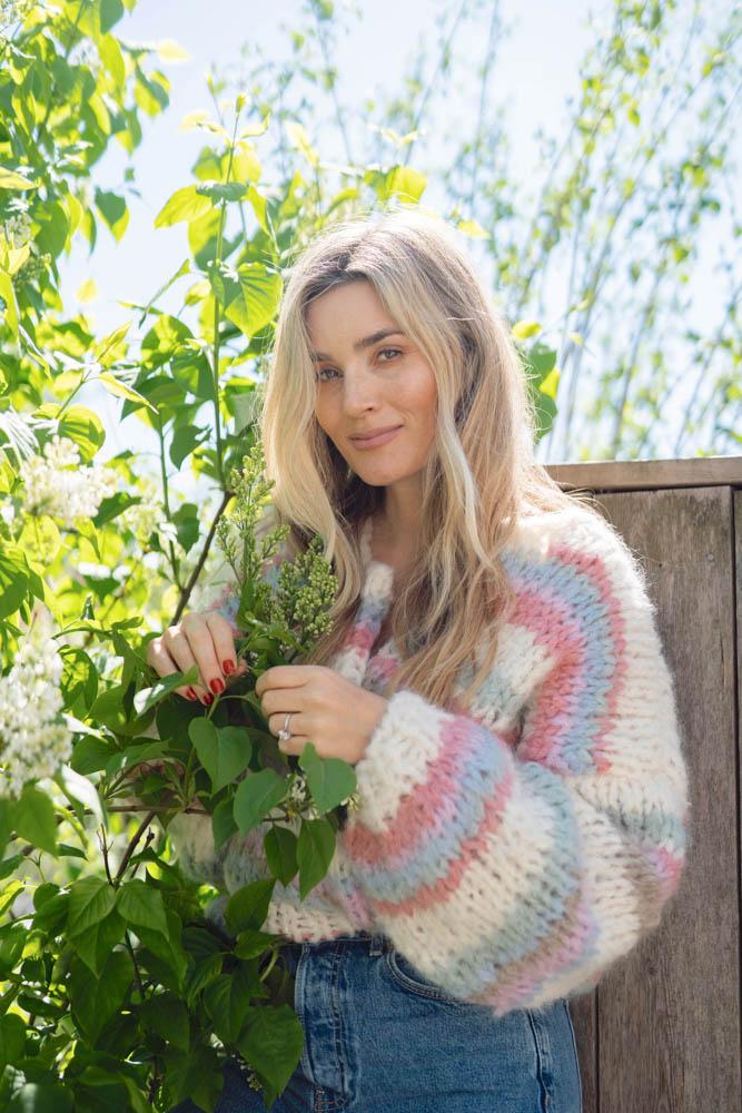Strikkepakken inneholder mønster og garn fra Camilla Pihl til Wildflower jakke strikket i Fnugg garn. Modellen i halvfigur og ser inn i kamera.