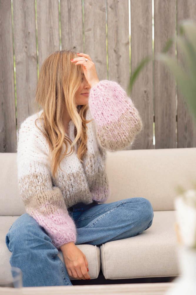 Strikkepakken inneholder mønster og garn fra Camilla Pihl til Crocus jakke som strikkes i Fnugg garn. Her i sommerpastellene perlerosa, greige og hvit. Modellen sitter på en sofa og ser mot høyre.