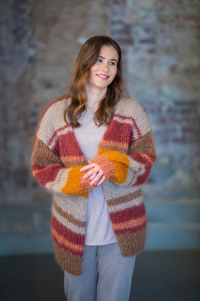 Strikkepakken inneholder mønster og garn fra Dalegarn til Pahsian cardigan som strikkes i Myk Påfugl. Bilde i front, modellen ser mot høyre.