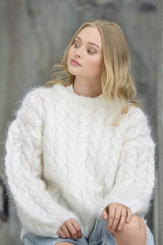 Strikkepakken inneholder mønster og garn fra Dalegarn til Melanita genseren som strikkes i Myk Påfugl. Modellen sitter.
