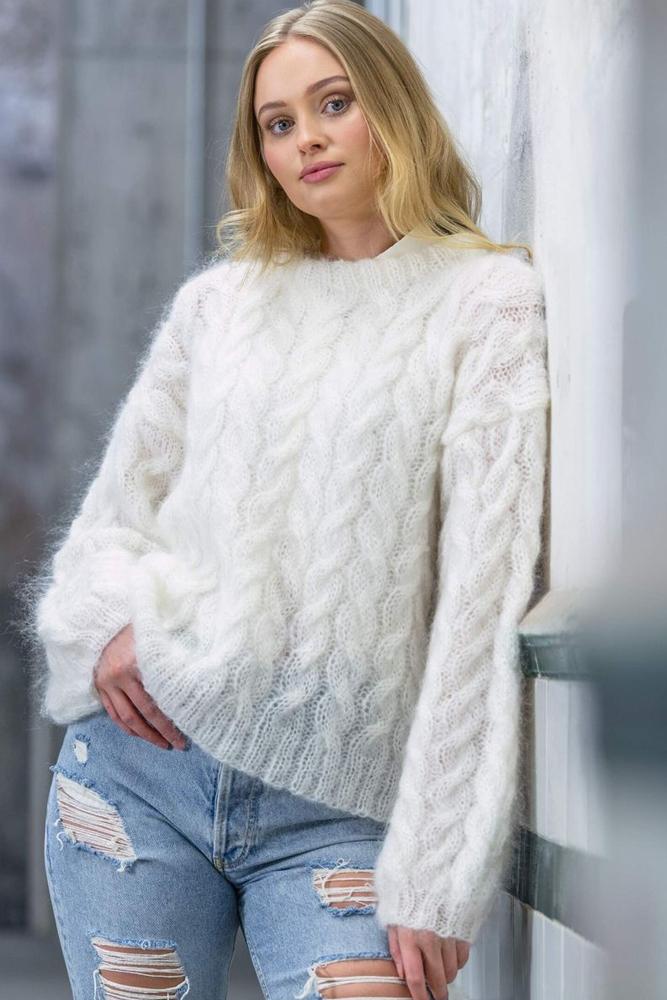 Strikkepakken inneholder mønster og garn fra Dalegarn til Melanita genseren som strikkes i Myk Påfugl. Bildet er i halvfigur.